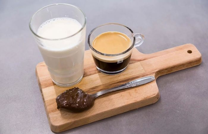 milk espresso in two separate glasses spoonful of hazelnut spread how to make iced coffee at home placed on wooden board