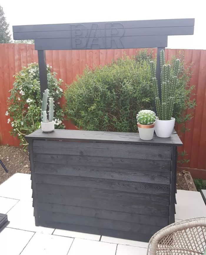 minimalistic bar made with black wood siding backyard bar ideas potted succulents on it