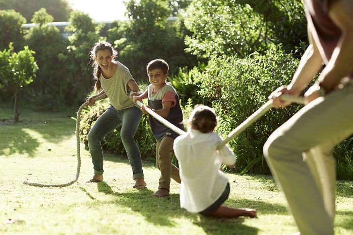 mom dad and kids playing tug of war outdoor fun for kids holding onto a rope on both ends
