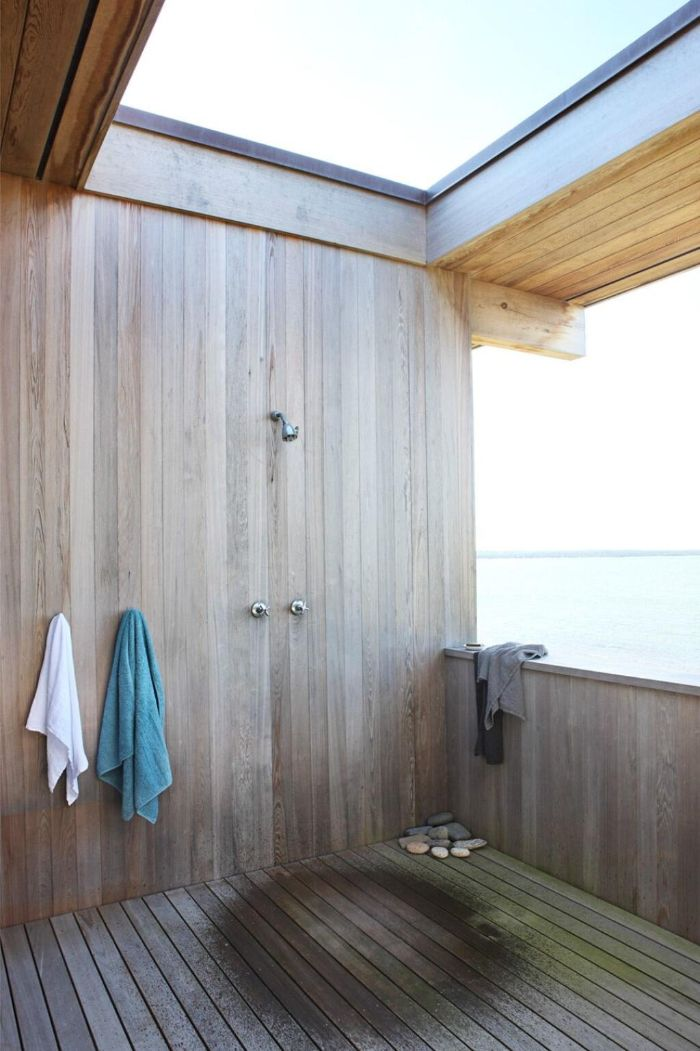 open ceiling and side outdoor shower enclosure made of wood with wood floor hooks for towels