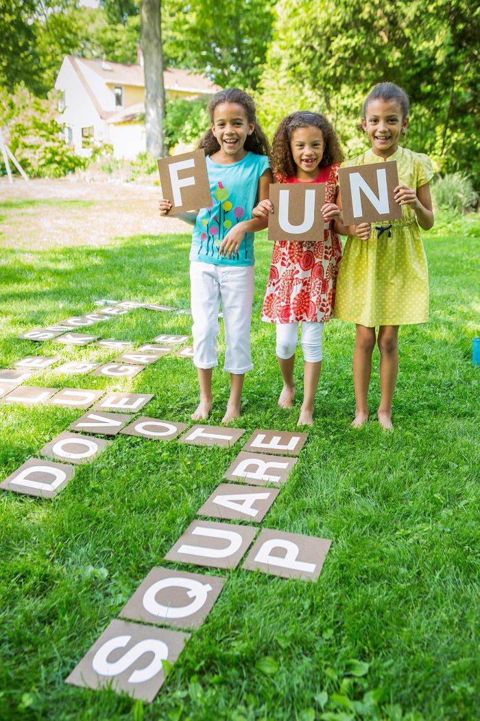 outdoor activities for toddlers three girls holding up boards with letters spelling fun outside scrabble