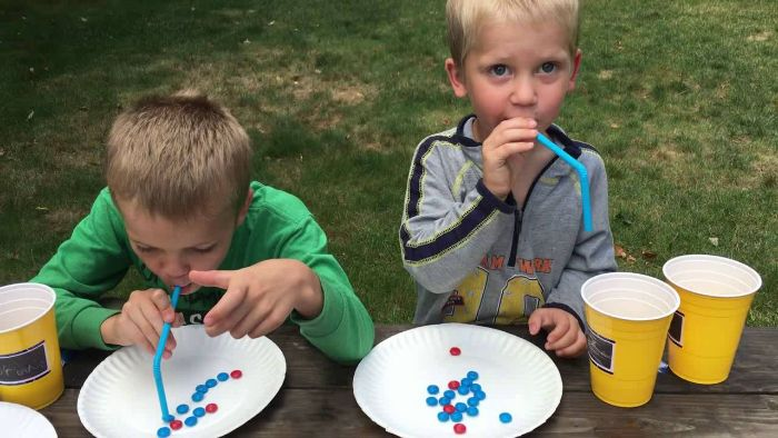 outdoor fun for kids two boys standing next to table trying to take candy from a plate with a straw