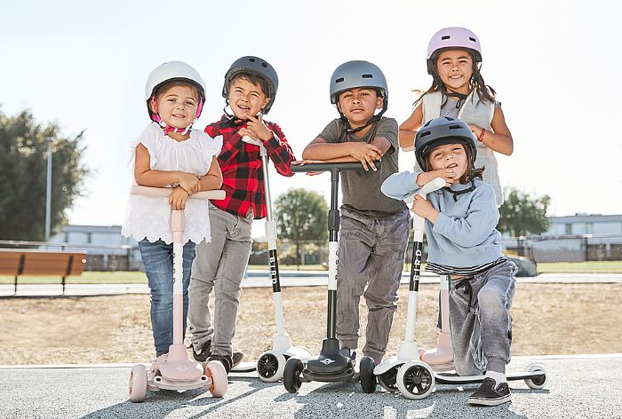 outdoor games for kids boys and girls wearing helmets riding scooters posing for a photo