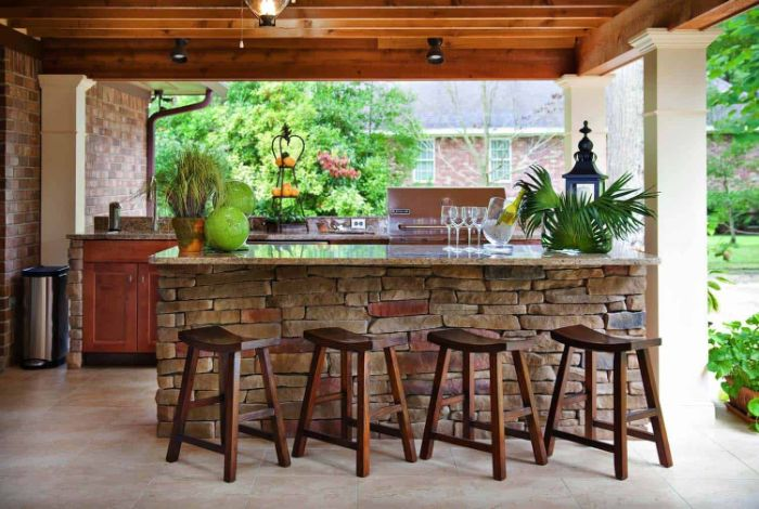 outdoor kitchen island made with stones outdoor patio bar black stoold in front of it wooden enclosure