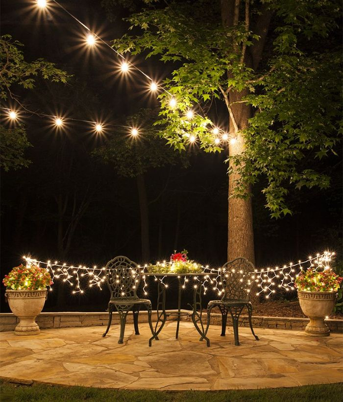 outdoor patio lights metal garden furniture fairy lights hanging from pots of plants strings of lights above hanging from tree