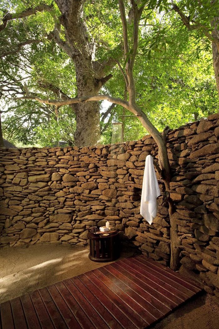 outdoor shower ideas wall made of rocks tree growing out of it shower with wood floor