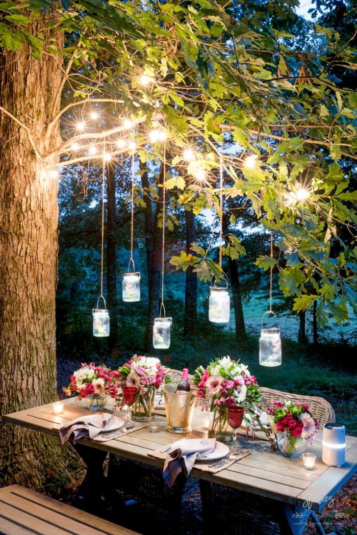 outdoor string lights wooden table and bench placed under a tree mason jars and string lights hanging above it