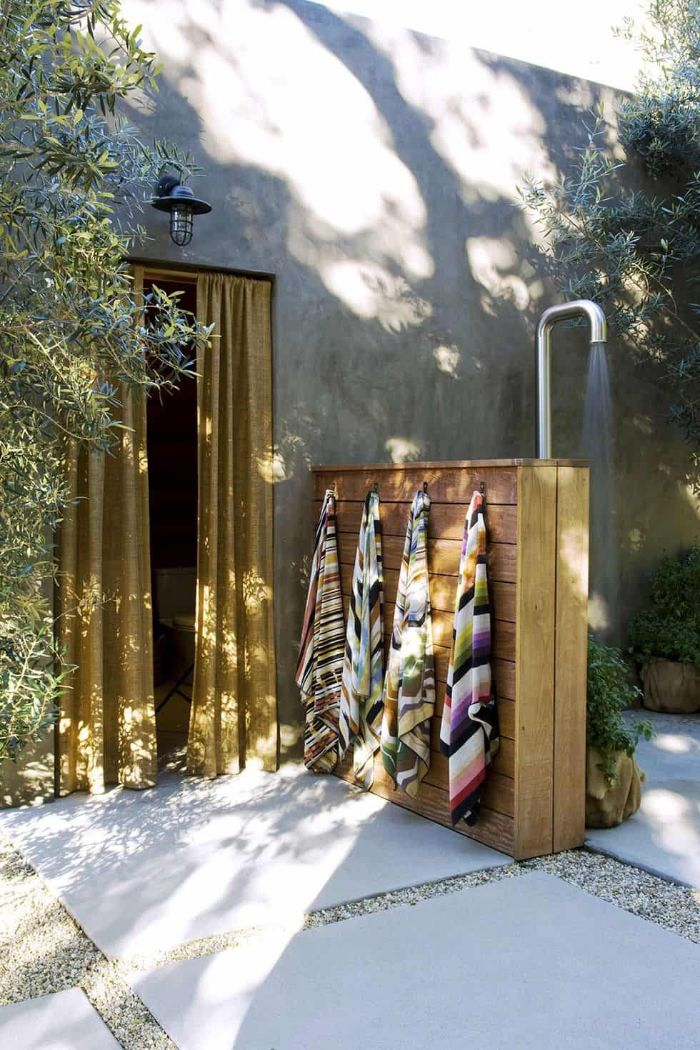 outside showers wood half wall with colorful towels hanging from it outside showers metal tube for shower