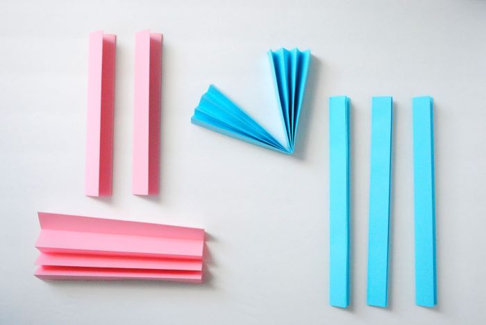 pink and blue paper folded as an acordeon placed on white surface baby shower centerpiece ideas step by step diy tutorial