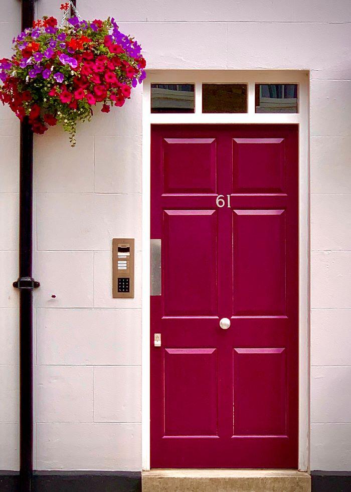 pink wooden door of house door installation large flower bouquet hanging above it