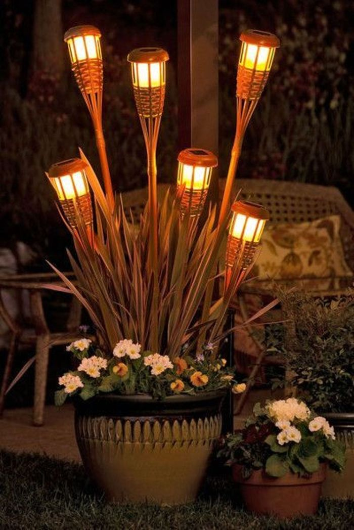 planters with flowers string light pole six solar panel torches stuck in them placed next to lounge area