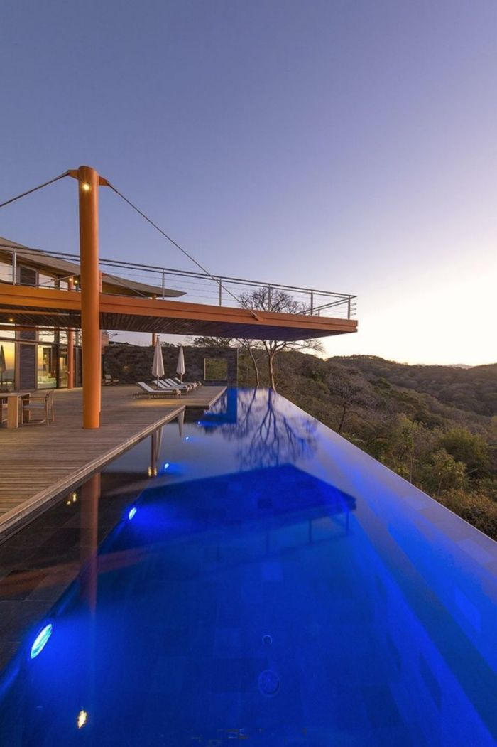 pool landscaping ideas infinity pool in the backyard of two storey house with deck lounge chairs and umbrellas