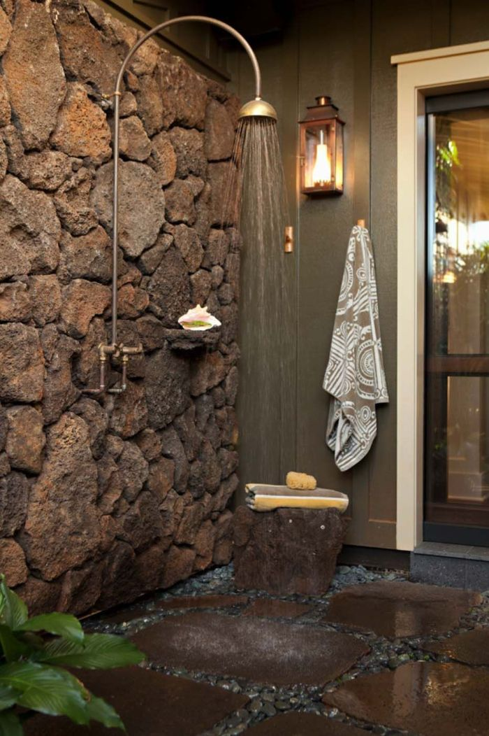 rock wall with vintage shower head and faucet outside showers stone tiles and small rocks on the floor