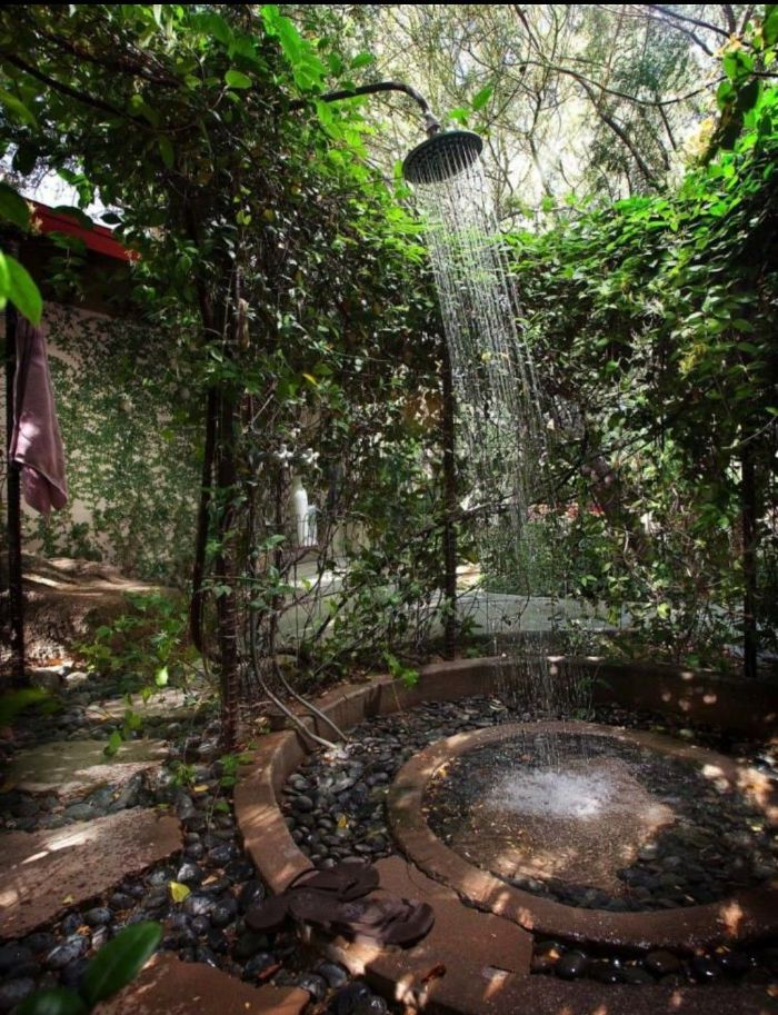 rocks and tiles on the floor freestanding outdoor shower surrounded by plants and greenery