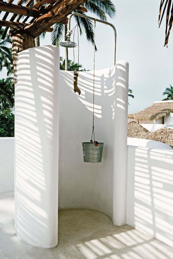 round enclosure in white how to build an outdoor shower bucket hanging from it underneath lots of palm trees
