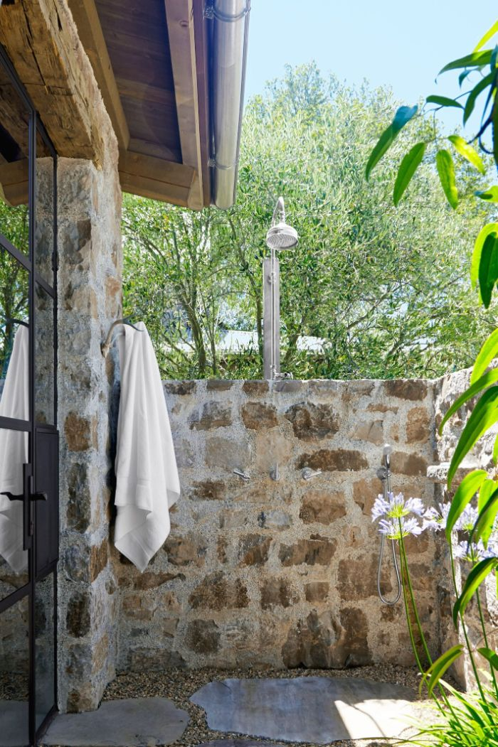rustic style wall made of stone how to build an outdoor shower shower head mounted on it towel hanging on the side
