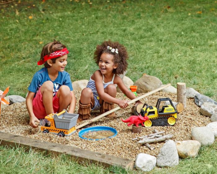 sandlot with toys and boulders around it outdoor activities for kids boy and girl playing inside