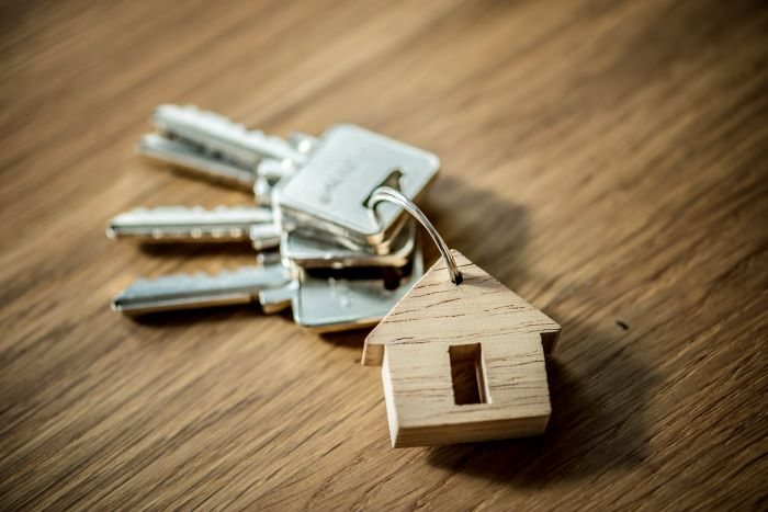 set of keys with a keychain in the shape of a house placed on wood surface house in spain