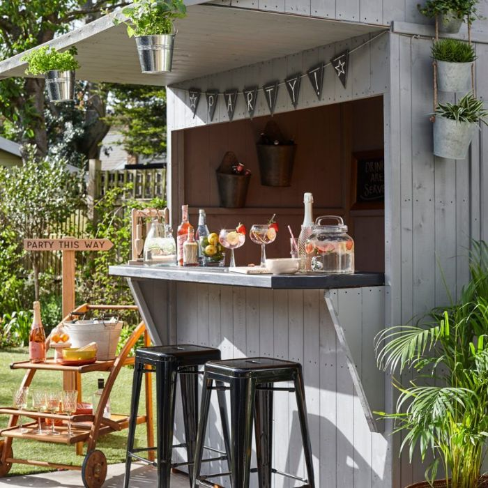 shed turned into bar made of white wood outdoor bar ideas two black stools in front mimosa cart