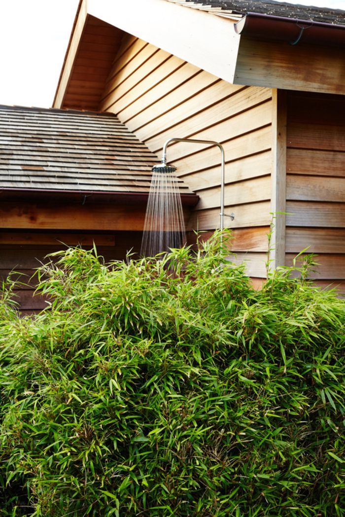 shower mounted on the wood wall on the side of the house outdoor shower designs hid behind bushes
