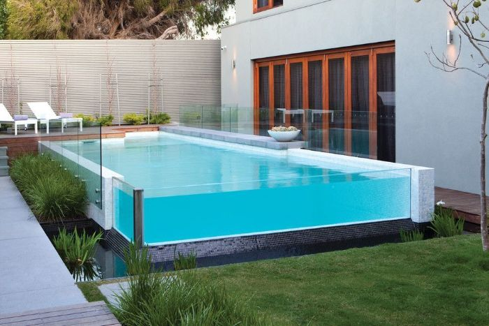 small above ground pool with glass walls small backyard pools two lounge chairs on deck next to it