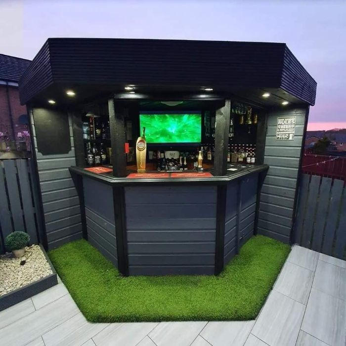 small garden bar made with black and grey wood outdoor bar ideas tv inside lots of bottles on the shelves