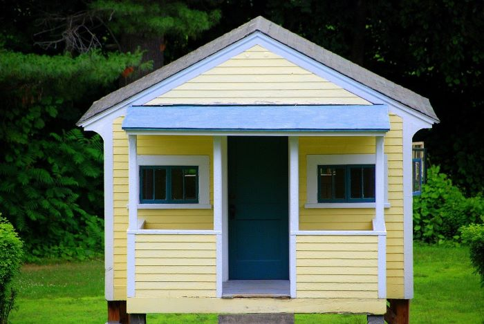 small house covered with yellow siding home siding blue frames on door windows roof