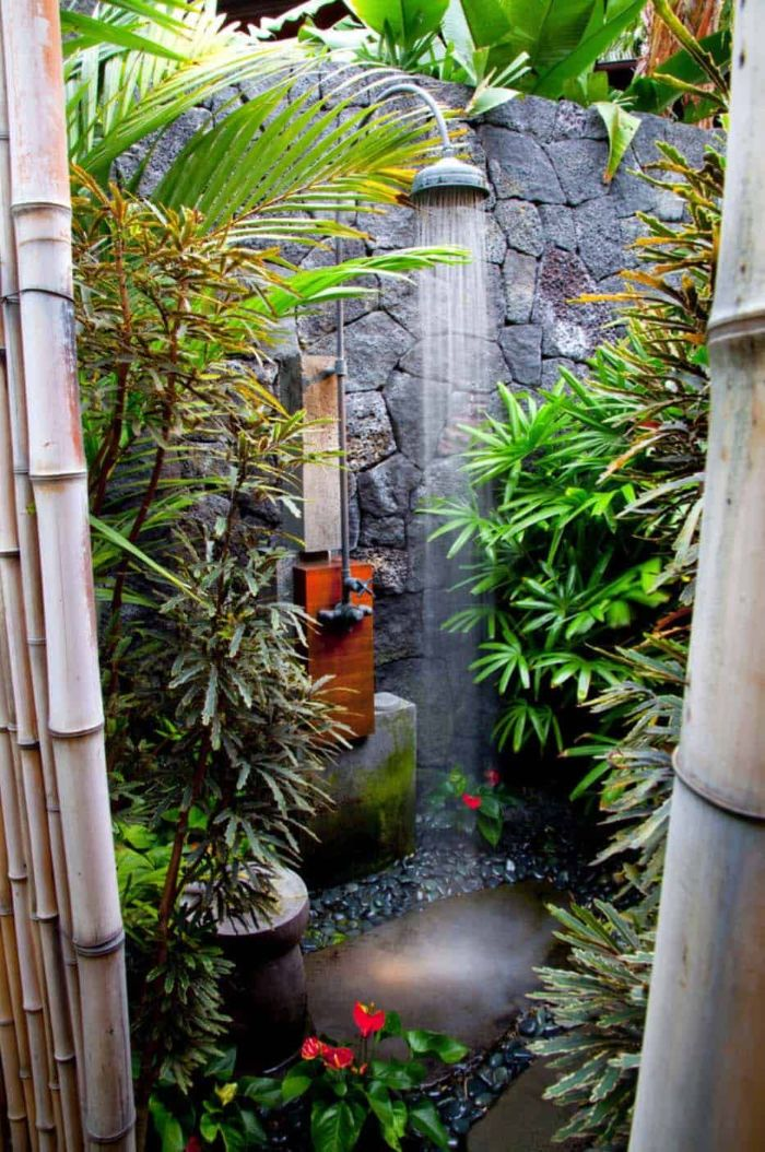 stone wall with shower mounted on it building an outdoor shower surrounded by plants