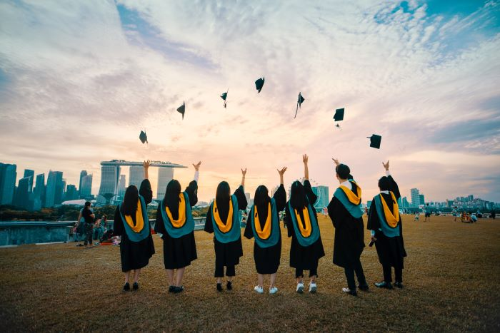 study architecture seven university students graduating throwing their hats in the air