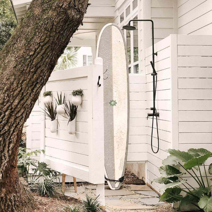 surf leaning on white wood enclosure how to build an outdoor shower black metal shower head pipes and faucet