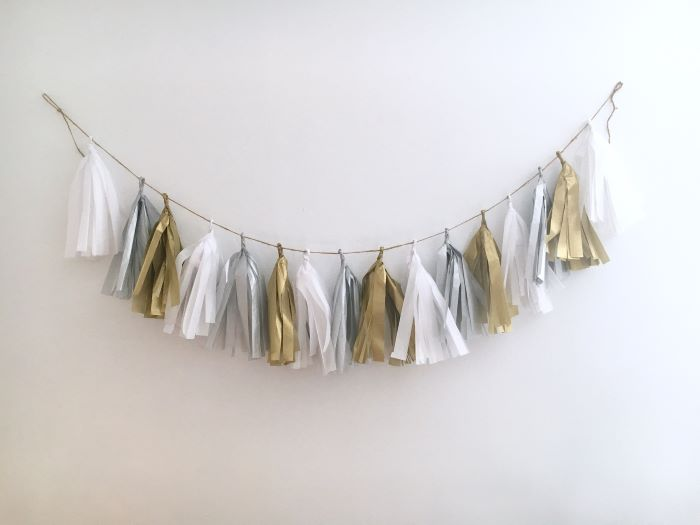 tassel garland in white silver and gold hanging on white wall baby shower centerpiece ideas