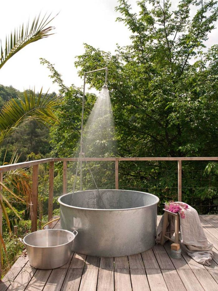 terrasse made of wood with large metal tub metal shower head on top outdoor shower enclosure