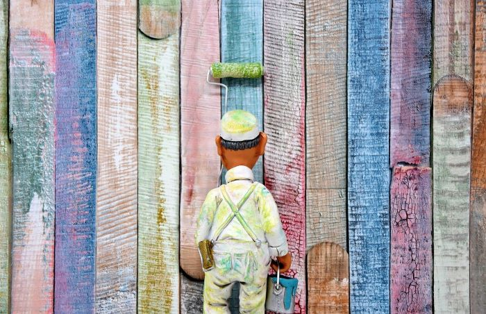 toy of man wearing protective gear and hat carrying a bucket of paint lead poisoning painting colorful wall