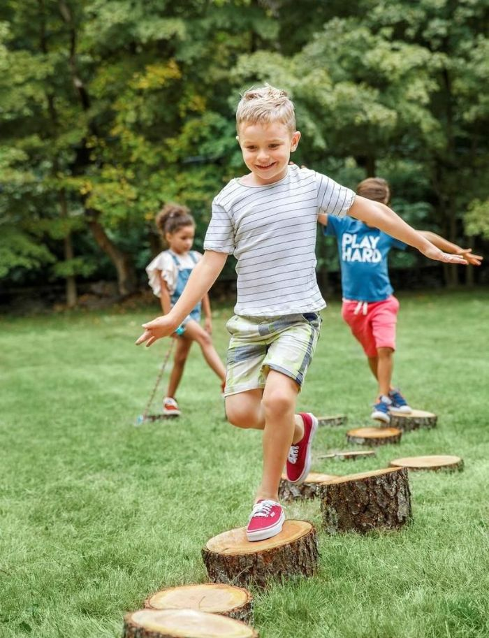 two boys and girl running on wooden logs outdoor activities for kids spread across field covered with grass