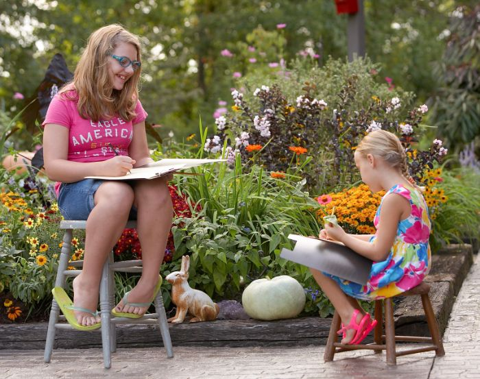 two girls different ages drawing outside outdoor activities for toddlers holding pencils sitting on chairs