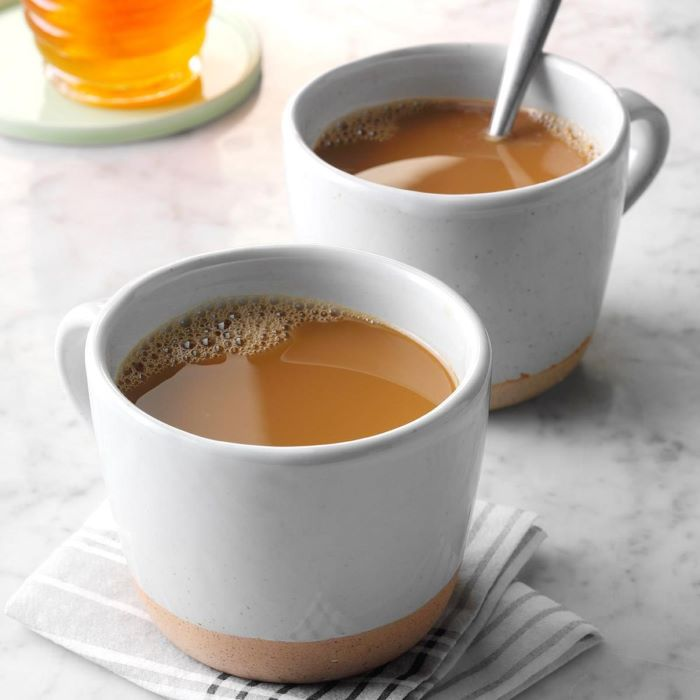 two mugs of coffee with milk cold brew coffee placed on white granite countertop