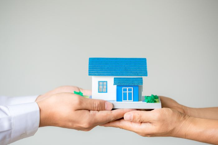 two people holding their hands out house in spain holding a house model