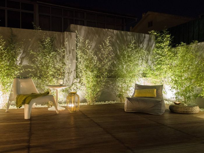 white and gray armchairs on wooden floor outdoor patio lights placed in the gravel under the planted bushes