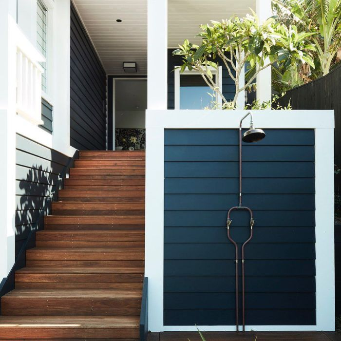 white and navy blue wood wall next to staircase building an outdoor shower metal shower mounted on it