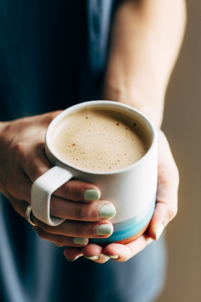 woman holding ceramic mug with turquoise nail polish coffee to water ratio cashew latte with milk foam