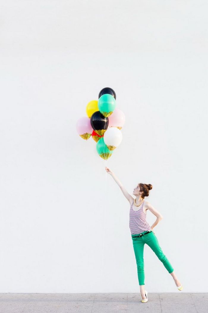 woman holding lots of balloons baby shower decoration ideas for girl blue black pink red yellow balloons