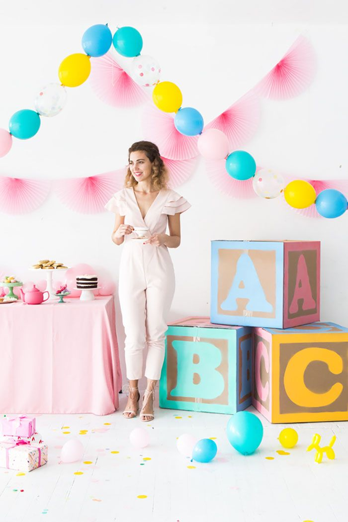 woman standing next to dessert table baby blocks baby shower decoration ideas for girl balloon garlands on the wall