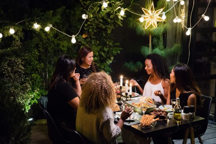 women sitting around table dining how to hang outdoor string lights strings of lights hanging from bushes around them