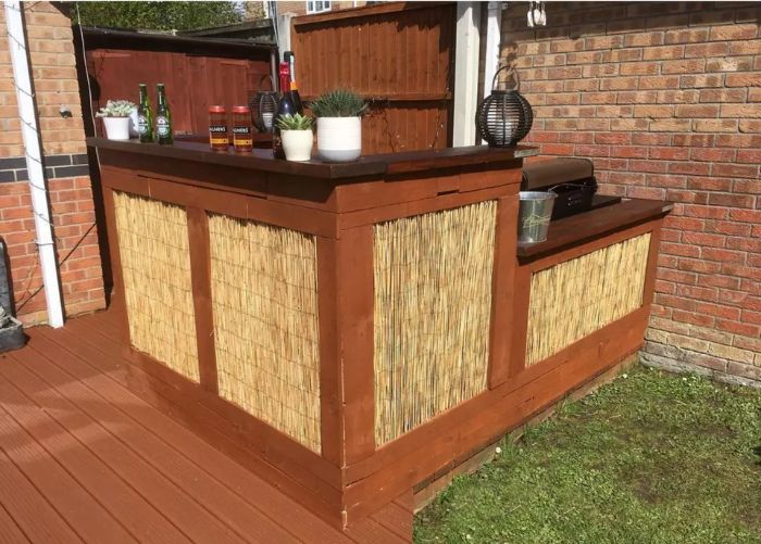 wooden bar with hay decorations on two levels different bottles plants on it outdoor wooden bar