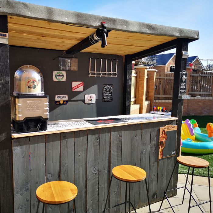 wooden enclosure in black with three bar stools diy outdoor bar next to kiddie pool