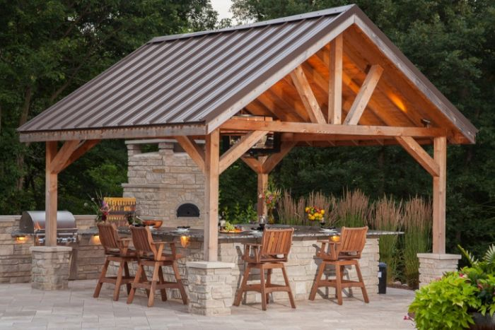 wooden enclosure over outdoor kitchen build with stone outdoor kitchen bar wooden chairs