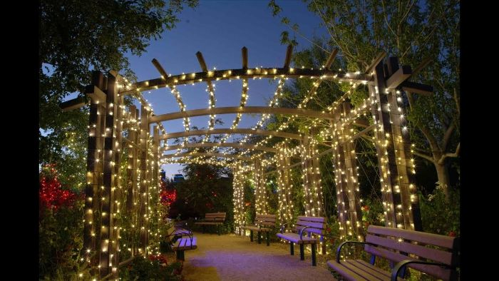 wooden poles above benches wrapped in strings of fairy lights landscape lighting ideas