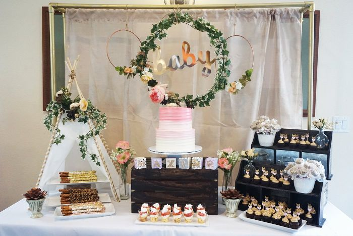 wreath with greenery and flowers hanging over dessert table baby shower decoration ideas pretzels cupcakes and cake