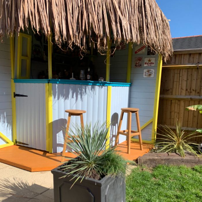yellow and blue enclosure with dried palm leaves on the roof backyard tiki bar two wooden bar stools