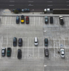 aerial photo of parking lot parking spot in the city half filled with parked cars